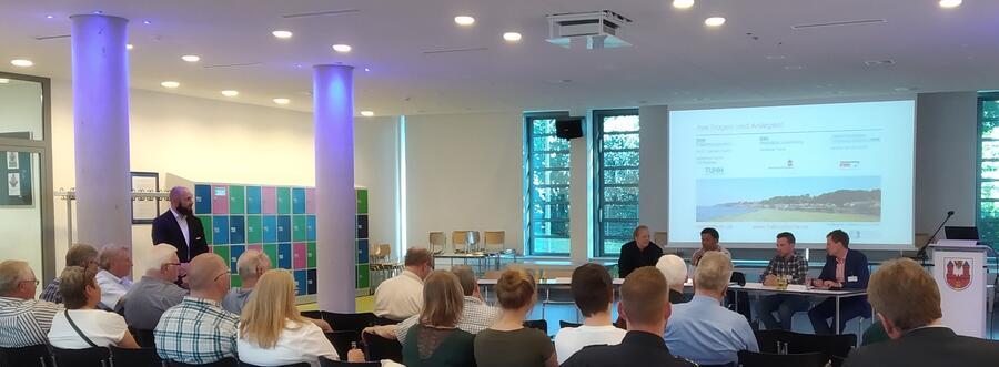 Prof. Dr. Carsten Gertz (Podium links)von der TUHH und Andrew Yomi (Podium, 2. Von links) vom Kreis Herzogtum Lauenburg diskutieren mit dem Publikum über Einsatzgebiete autonomer Fahrzeuge im öffentlichen Personennahverkehr